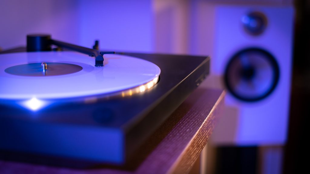 Turntables in blue light with a speaker